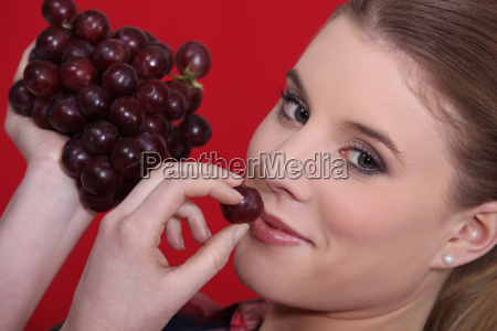 portrait of blonde eating red grapes