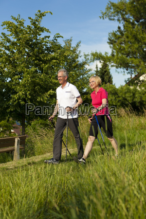 happy elderly couple nordic walking in