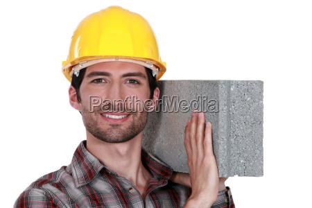 mason carrying a brick on his