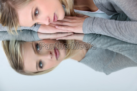 blonde woman looking her reflection in
