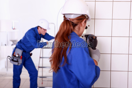 female electrician using a power drill