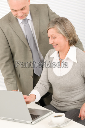 happy senior businesspeople looking at computer