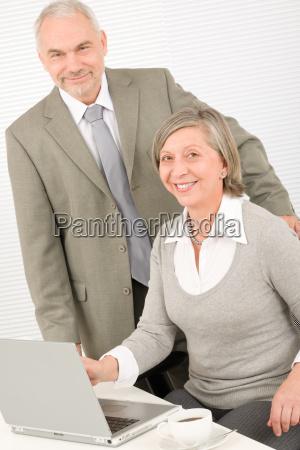 senior businesspeople in office work on