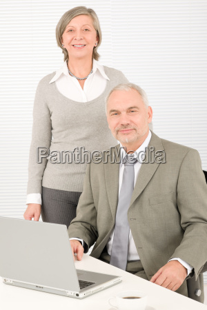 senior businesspeople behind office table computer