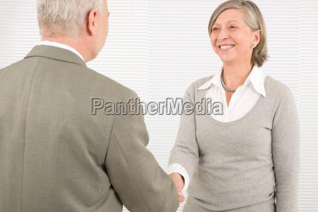 senior businesspeople handshake professional smile