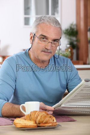 middle aged man reading newspaper whilst