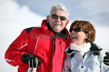 happy couple in snowsuits