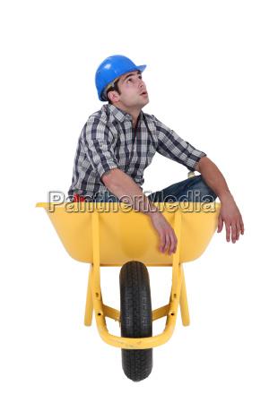 foreman sitting in wheelbarrow isolated on