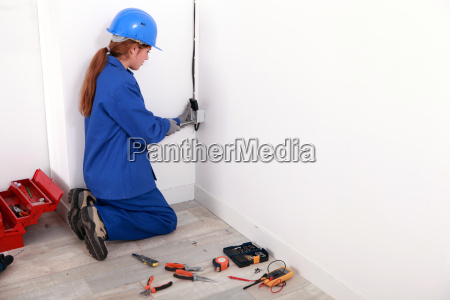 female electrician fixing wall socket