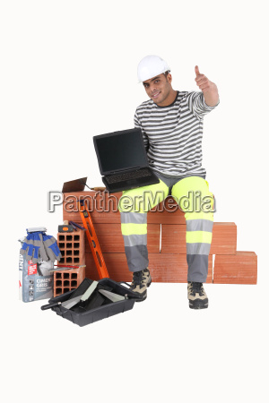 builder with a laptop showing a
