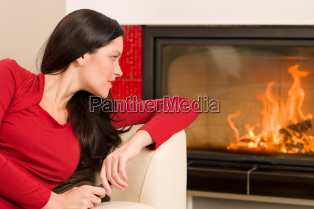 attractive woman looking into fireplace cozy
