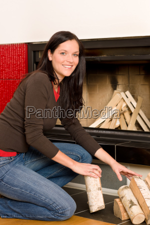 home fireplace woman put logs happy