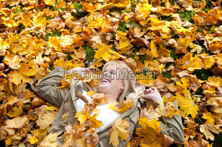 cheerful teenager in autumn foliage