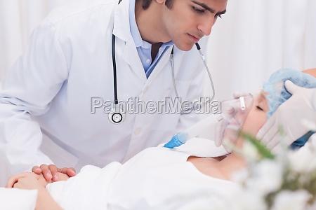 doctor examining intensive care patient
