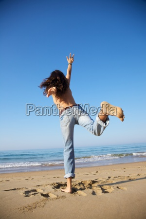 woman reachs sky at beach