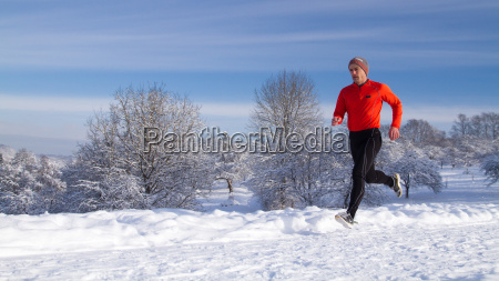 jogger in snowy winter landscape