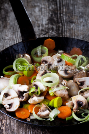 iron pan with vegetables on wood