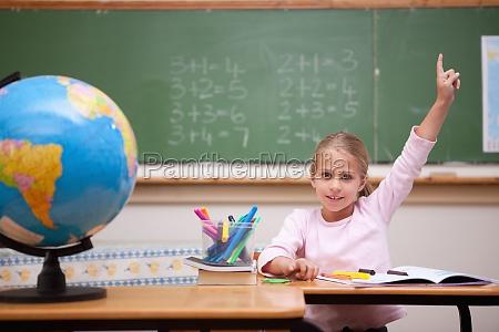 cute schoolgirl raising her hand to