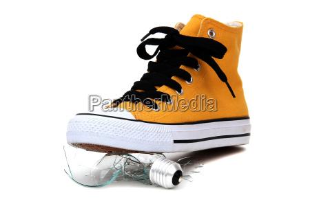broken bulb under sneaker