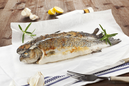 two grilled trouts with fresh herbs