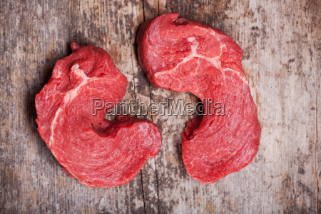 two raw steaks on a wooden
