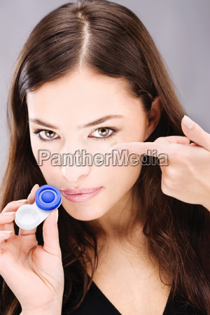 young woman holding contact lenses cases