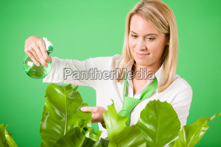 green business woman water houseplant smiling