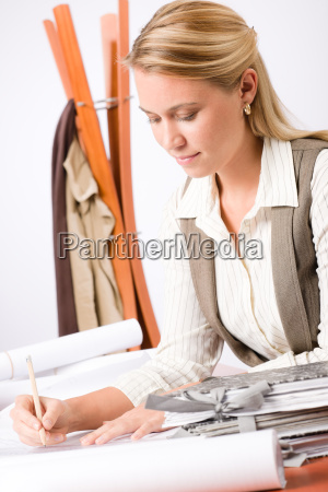 architect woman sketches office with blueprint