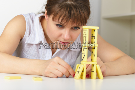 young woman accurately builds tower of