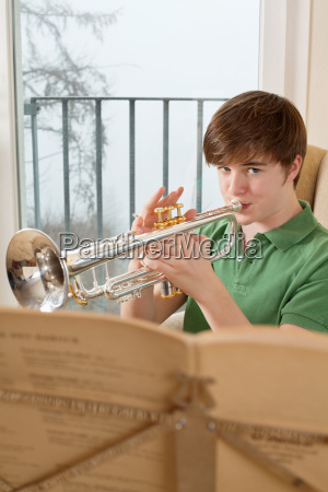 male teenager playing the trumpet