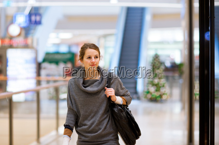 young woman looking at store windows