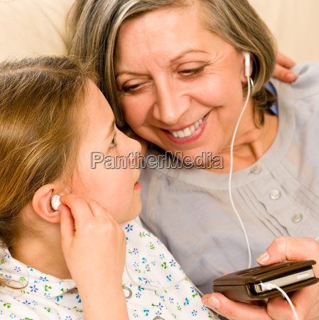 grandmother and young girl listen music