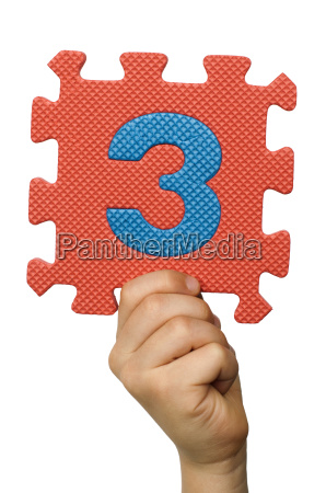 children hand holding the number three