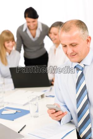 businessman use phone during team meeting