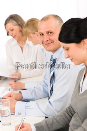 smiling businessman behind desk during team