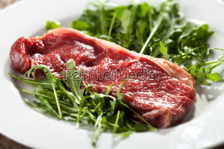 raw sirloin steak on rocket