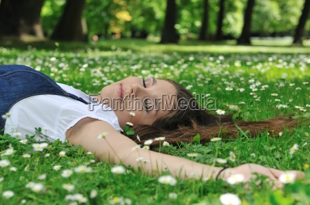 young woman lying in grass with
