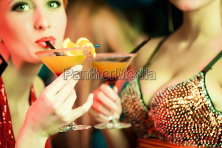 women in a club drinking cocktails