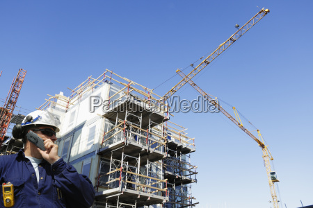 site worker with cranes and scaffoldings