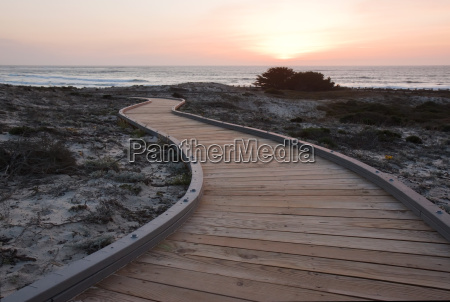 sunset over a walkway through sand