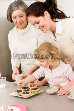daughter and mother decorating cupcakes sprinkles