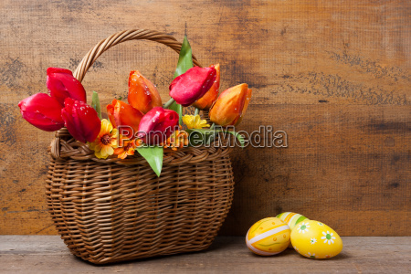 basket with silk flowers next to