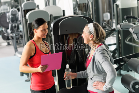 personal trainer with senior woman at