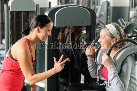 personal fitness trainer with senior woman