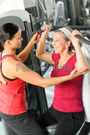 personal trainer assist senior woman at