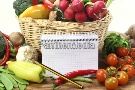 shopping list with pencil and vegetables