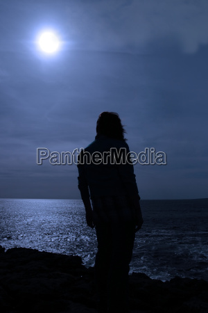 silhouette of lone woman on cliff