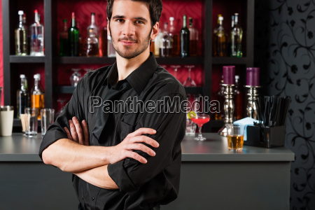 barman in black standing at cocktail