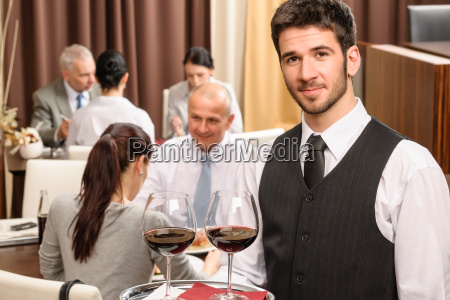 waiter hold wine glasses business lunch