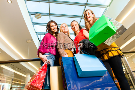 four girlfriends shopping in a mall
